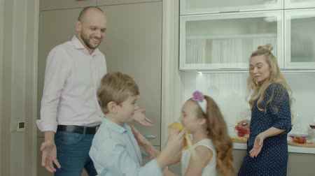 kalmak : Mischievous little siblings playing in the kitchen while stay-at-home mother preparing family breakfast in domestic kitchen in the morning. Casual family with children during food preparation at home.