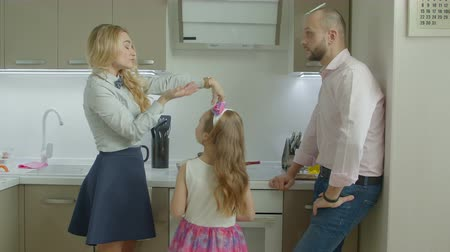 поздний завтрак : Busy businesswoman in formal wear being late to work, checking the time and complaining about unprepared morning breakfast while handsome man with cute daughter cooking in domestic kitchen. Стоковые видеозаписи
