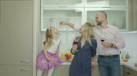 slanina : Carefree family with adorable daughter enjoying leisure in domestic kitchen during weekend. Playful father with glass of red wine feeding slice of bacon to his little girl while relaxing at home. Dostupné videozáznamy
