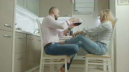 cherish : Relaxed romantic couple in love enjoying leisure and drinking tasty red wine in domestic kitchen during weekend. Affectionate chatting spouses cherishing every moment together at home. Stock Footage