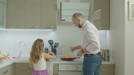 omlet : Positive caring father and adorable little daughter preparing delicious omelet for morning breakfast in domestic kitchen. Lovely elementary age girl helping single dad to cook at home. Stok Video