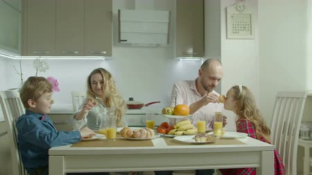 kahvaltı : Joyful carefree family with two elementary age children having fun, staining noses with cream and laughing while enjoying healthy morning breakfast in domestic kitchen during weekend.