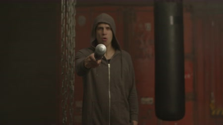 гангстер : Aggressive grim looking hoodlum in hoodie with outraged look pointing baseball bat at camera over dark industrial gym background. Violent mean guy pointing baseball bat with threatening look indoors. Стоковые видеозаписи