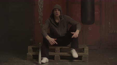 significar : Grim hooligan in hoodie aggressively gesturing in industrial premises while sitting on pallet. Angry looking hoodlum showing intimidating gestures , expressing aggression and brutality.