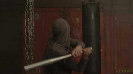 significar : Rear view of cruel mean street hoodlum in hoodie hitting victim with baseball bat in industrial premises. Aggressive rude male thug attacking with sport bat and beating up someone indoors. Stock Footage