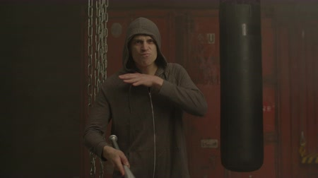 grim : Furious mean man in hoodie pointing aggressively with baseball bat and showing intimidating gesture- cutting throat in industrial premises. Grim hoodlum holding baseball bat and threatening someone.