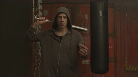 médio : Dangerous street hooligan in hoodie threatening with baseball bat and gesturing come here with furious aggressive look in industrial premises. Mean guy with baseball bat ready to attack indoors.