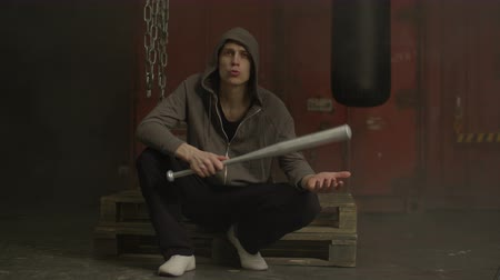 significar : Grim mean hooligan in hoodie holding baseball bat and threatening someone while sitting in industrial space. Young aggressive hoodlum with baseball bat in hands ready to attack. Stock Footage