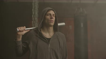 médio : Grim looking hoodlum in hoodie holding baseball bat, walking with aggressive threatening look. Brutal street thug with baseball bat, expressing hostility, rage and danger in industrial foggy primeses.
