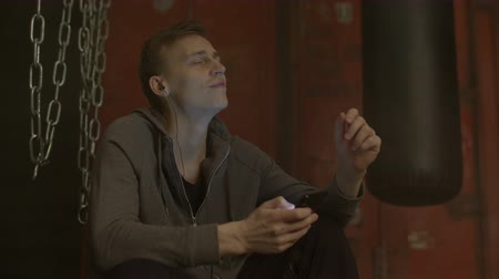 selecionar : Handsome man in earphones choosing favorite music on smart phone player in garage gym. Cheerful guy in hoodie checking playlist of audio application on cellphone and listening to music indoors.