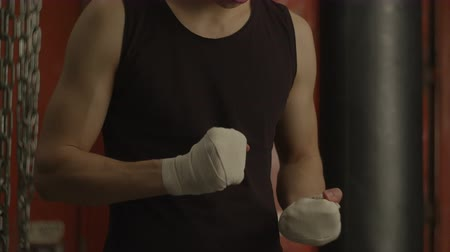 кулак : Motivated muscular fighter preparing for sport training in garage gym. Concentrated male boxer checking his fists wrapped with boxing wraps, ready for sparring and exercising in back-block gym.