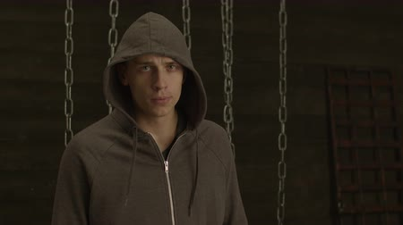 médio : Portrait of determined hooligan in hoodie standing against iron chains and brick wall background, looking aggressive and threatening in dark abandoned building. Mean tough thug posing indoors. Stock Footage