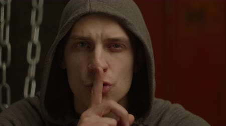 significar : Dangerous man in hoodie with aggressive look making silence sign in violent and threatening way over dimmed abandoned building background. Mean hoodlum showing hush gesture, dont make noise, be quiet Vídeos