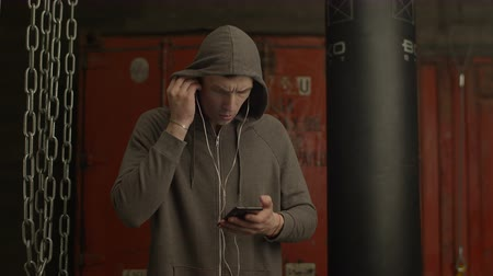 stanovena : Concentrated man in hoodie setting up music on smart phone app before sport training in gym. Determined male athlete in headphones choosing music set for workout with mp3 player on cellphone indoors.