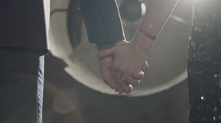 together trust : Close-up of affectionate reliable couple in trendy clothes holding hands expressing love, care, compassion and support in relationship over dimmed industrial background in rays of rising sun. Stock Footage