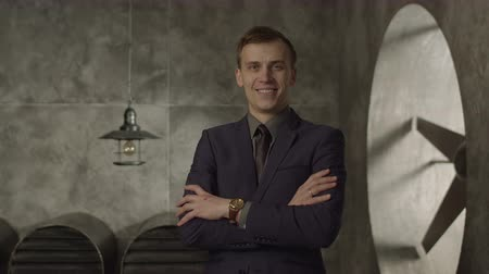 сияющий : Cheerful handsome businessman in formal wear standing arms crossed and smiling, expressing confidence and success. Positive adult entrepreneur with folded hands posing with beaming smile indoors.