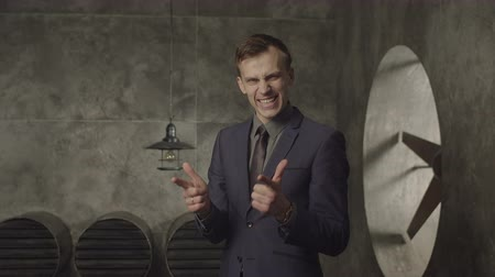 сияющий : Happy successful entrepreneur with beaming smile pointing aside with fingers, making winning gesture. Cheerful businessman showing hand gesture, expressing positivity and joy after achievement goal. Стоковые видеозаписи