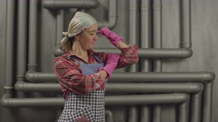 dienstbode : Cheerful strong housewife in apron wearing cleaning gloves, showing bicep and smiling. Positive housekeeper woman in rubber gloves flexing biceps muscles, feeling strength and determination.