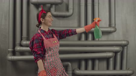 headband : Smiling cleaning woman wearing headband, apron and protective gloves, spraying cleaning detergent on surface during housework. Cheerful housewife with cleaning spray bottle doing cleanup.