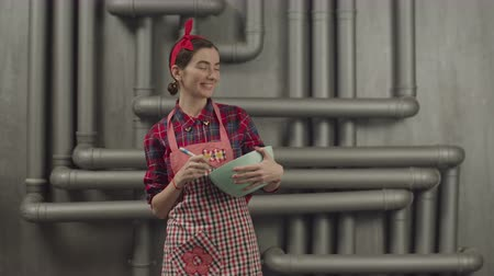 headband : Positive joyful housewife in apron and headband making dance moves while stirring mixture into bowl with whisk. Carefree lovely woman listening music and dancing while cooking indoors.