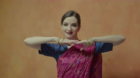 dobrável : Attractive woman in traditional colorful indian sari with bindi folding arms in parallel touching fingertips and making head movements. Smiling female winking which means invitation to love game.