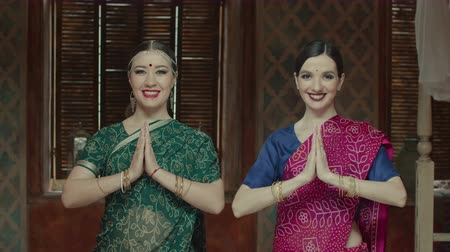 handen ineen : Two females in colorful ethnic indian sari and bindi points on forehead joining hands in namaste, traditional hindu greeting. Attractive women with charming smiles expressing respect and hospitality.