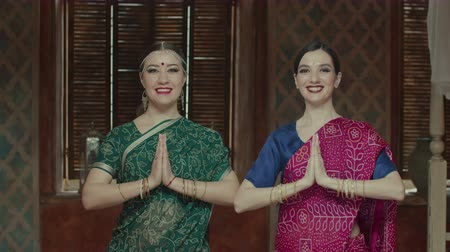 smilies : Cheerful females in colorful ethnic indian sari with bindi points on forehead looking at camera with beaming smilies, expressing respect by connecting hands in namaste, traditional hindu greeting.