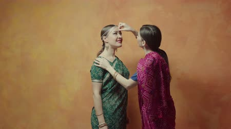 посвящение : Two women in colorful ethnic indian dresses sari with bracelets and tika decoration preparing for hindu initiation ceremony. Helpful female sticking red bindi point on forehead of charming friend. Стоковые видеозаписи