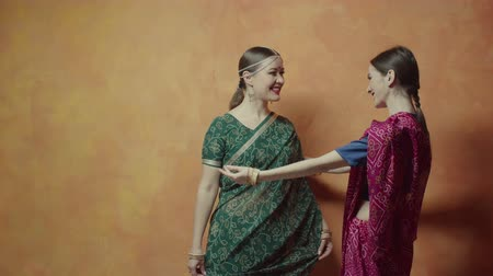 čelo : Two charming women in colorful traditional indian clothing saree with bindi points, many bracelets and tika decoration ready for hindu initiation ceremony. Caring female finally looking at friend.