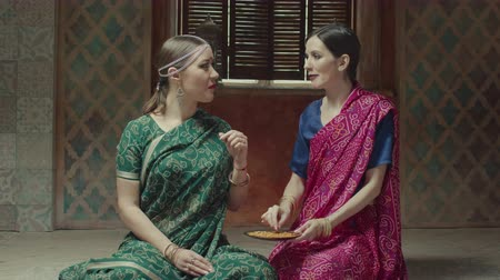 exotic dishes : Seated on floor attractive women in hindu dress sari with bindi and traditional jewels eating with hands. Lovers of indian cuisine enjoying flavor of ethnic delicious meal, Bombay mix with appetite.