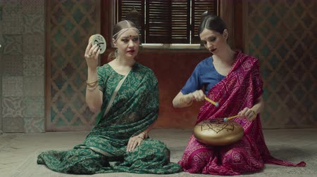 přadeno : Two females holding in arms traditional meditative instruments sitting on floor in oriental interior. Calm women in hindu sari, jewelry playing kanjira and tank drum with written mantra om symbol.