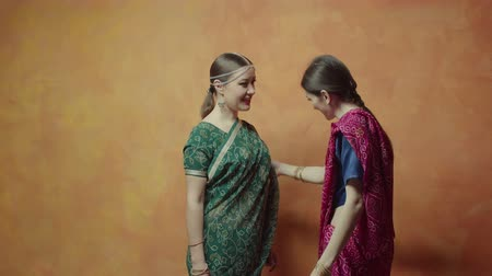 indie : Worried before hindu initiation females in traditional indian clothing with bracelets and tika decoration talking while fitting saree. Caring friend calming young woman and assuring in her beauty.