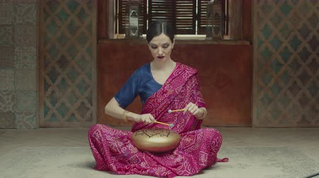 přadeno : Attractive female performing traditional indian music using hank drum with signed om symbol while sitting on floor in home interior. Focused woman drummer in hindu sari playing glucophone by drums.