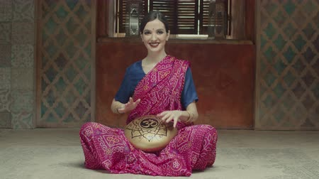 přadeno : Affectionate woman playing ethnic indian music using tank drum with om sign. Pacified female in hindu dress sari with bindi and bracelets drumming rhythm by hands on hank drum sitting on floor at home