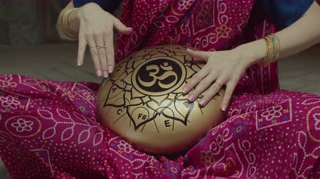 přadeno : Midsection of seated in lotus pose woman playing traditional indian music using glucophone decorated with mantra symbols. Dressed in sari female drumming rhythm on hank drum by hands with bracelets. Dostupné videozáznamy