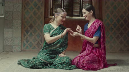 admirado : Conquered by aroma women sniffing wonderful flavor of dry perfume while sitting on floor at home. Charming females in traditional indian sari and jewelry one by one applying sachet with great pleasure Stock Footage