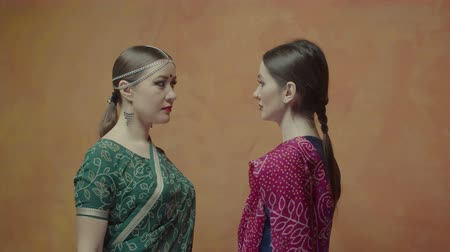 bijuteria : Beautiful females in ethnic hindu clothing sari with bindi and tika decorations meeting indoors. Women rivals burning one anothers eyes fighting for attention of beloved man.