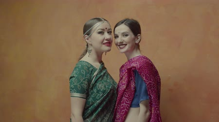 bijuteria : Seductive women with charming smiles in traditional indian dress sari with bindi points and tika decorations tilting heads together. Positive females demonstrating friendship and happiness.