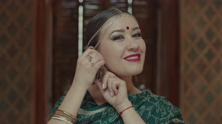 аксессуары : Portrait of attractive female putting massive golden earrings and charmingly smiling. Confident in her beauty woman in indian sari, jewelry with bindi and eastern makeup admiring herself in mirror.