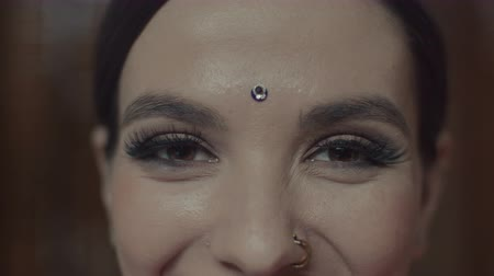 čelo : Close-up of beautiful female face with wide open brown eyes, long clapping eyelashes, bright makeup and bindi point on forehead. Smiling hindu style woman hypnotizing with fascinating gaze.