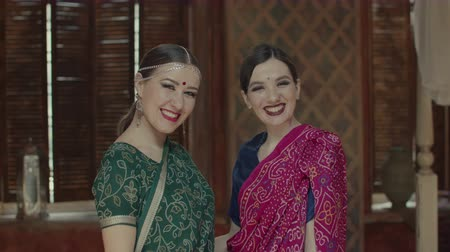 kacérkodás : Happy female friends in traditional hindu sari and jewelry with bindi points, bright eastern makeup and burning eyes seductively laughing. Stunning indian style women emitting happiness, joy.