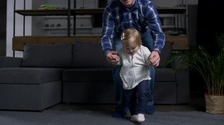 segítség : Close-up of adorable little kid confidently walking with caring fathers help. Dad holding beloved daughter supporting with walk and cheerful toddler actively stepping on floor in living room.