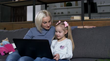 öğrenme : Little preadolescent daughter doing tasks in digital notebook online with moms help. Loving mother with preschool girl using laptop for distance education while sitting on couch in domestic interior. Stok Video