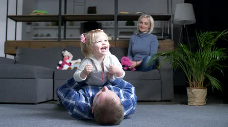 harmonia : Caring father lying on the floor, lifting up and kissing cheerful little girl while happy mother looking at them with love in background. Dad with laughing child having fun and communicating at home. Wideo