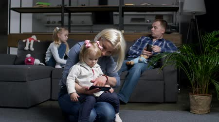 abandonment : Modern family using smart technology devices separately from each other. Mother with toddler daughter watching cartoon on cellphone, father networking on smart phone, preschool girl feeling abandoned. Stock Footage