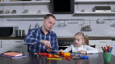 alicate : Caring father with toy set explaining to little girl use of different work tools while sitting at table in domestic kitchen during shop class. Dad teaching kid handling with tools at home craft lesson Stock Footage