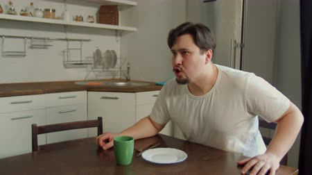 výrazy : Aggressive jealous husband swearing with wife, blaming for treason and threatening with violence sitting at kitchen table. Ferosious man yelling, getting up from chair, banging on table with anger. Dostupné videozáznamy
