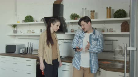 jealous : Jealous wife listening conversation of playful husband standing with cellphone in home kitchen. When angry woman requiring explanations , communicating with mistress man starting to make excuses. Stock Footage