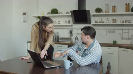 ashamed : Surprised woman seeing confused husband sitting at kitchen table, chatting online with mistress on laptop. Angry female caught ashamed man viewing embarrassing content online, requiring explanations. Stock Footage