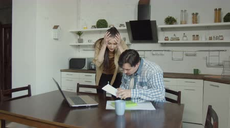 stres : Anxious wife showing foreclosure notice to husband planning budget online on laptop while sitting in domestic kitchen. Man with horror reading eviction notice received due to non-payment of home loans Dostupné videozáznamy